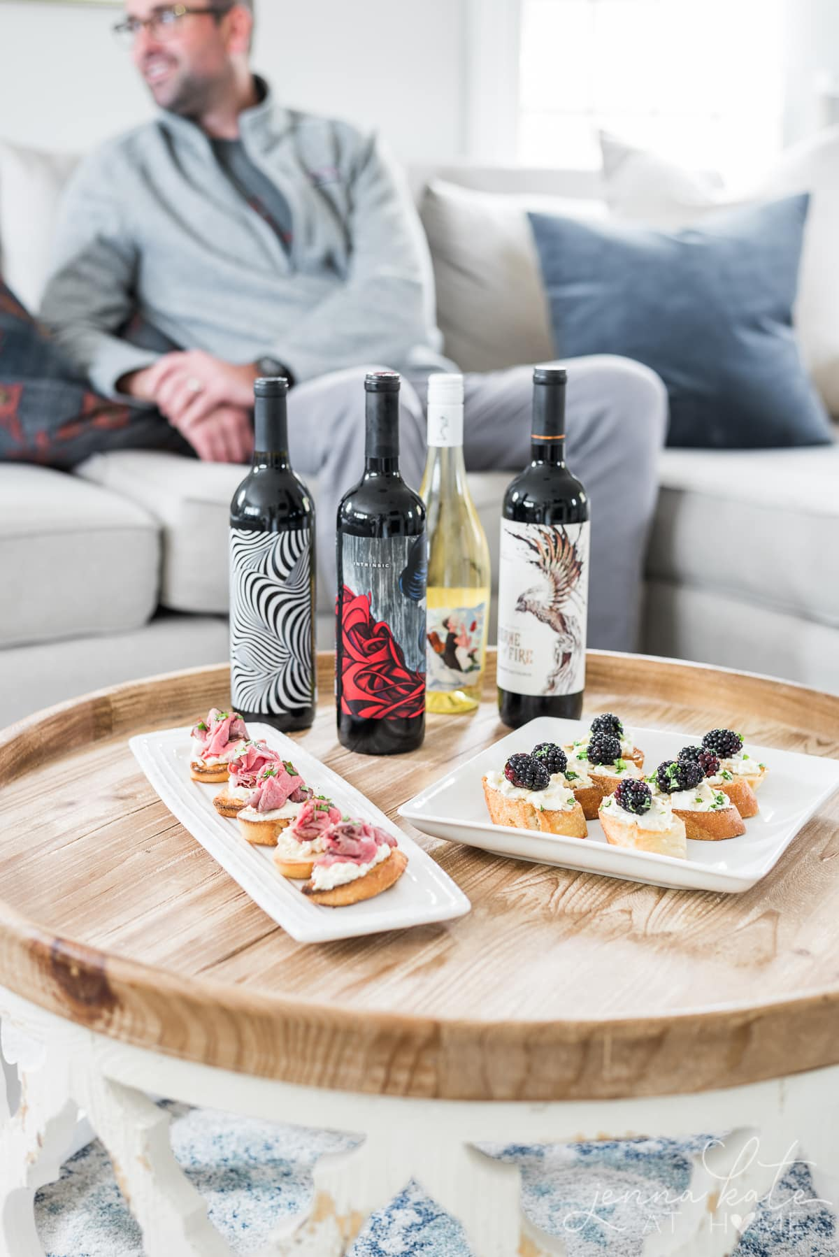 Various bottles of red and white wine on a coffee table with appetizers