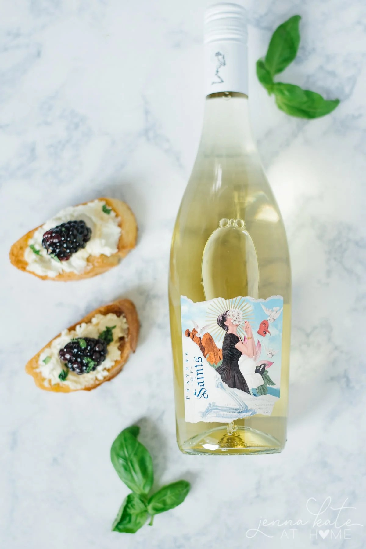 Bottle of white wine paired with fruit and goat cheese crostini