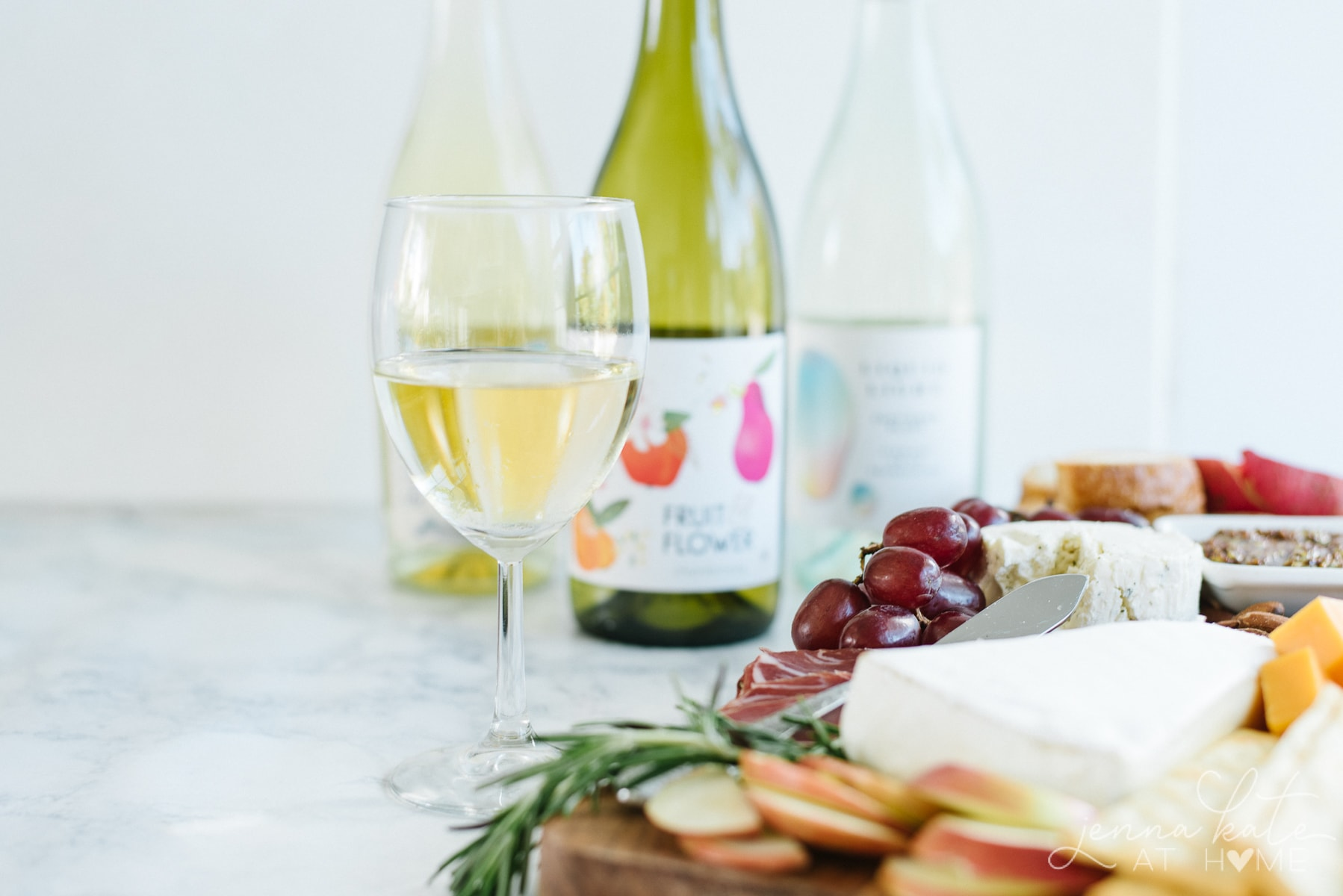A glass of Sauvignon Blanc alongside a charcuterie board
