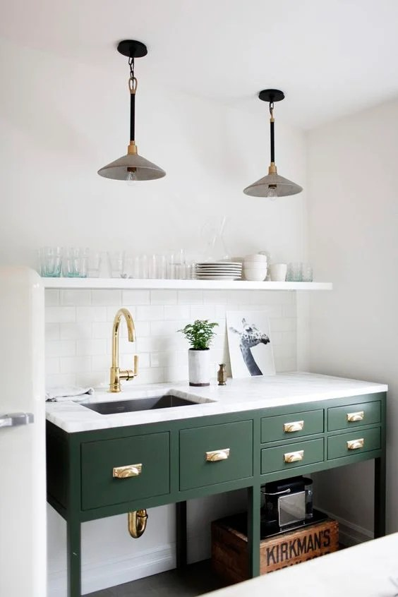 Kitchen island painted green shiny with brass hardware and faucet