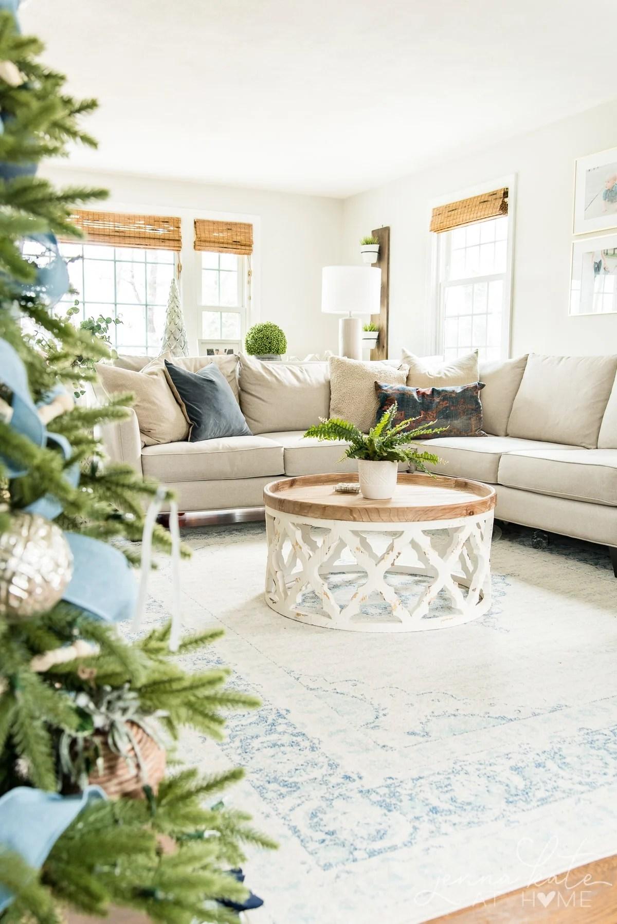 View of the living room peeking through the Christmas tree