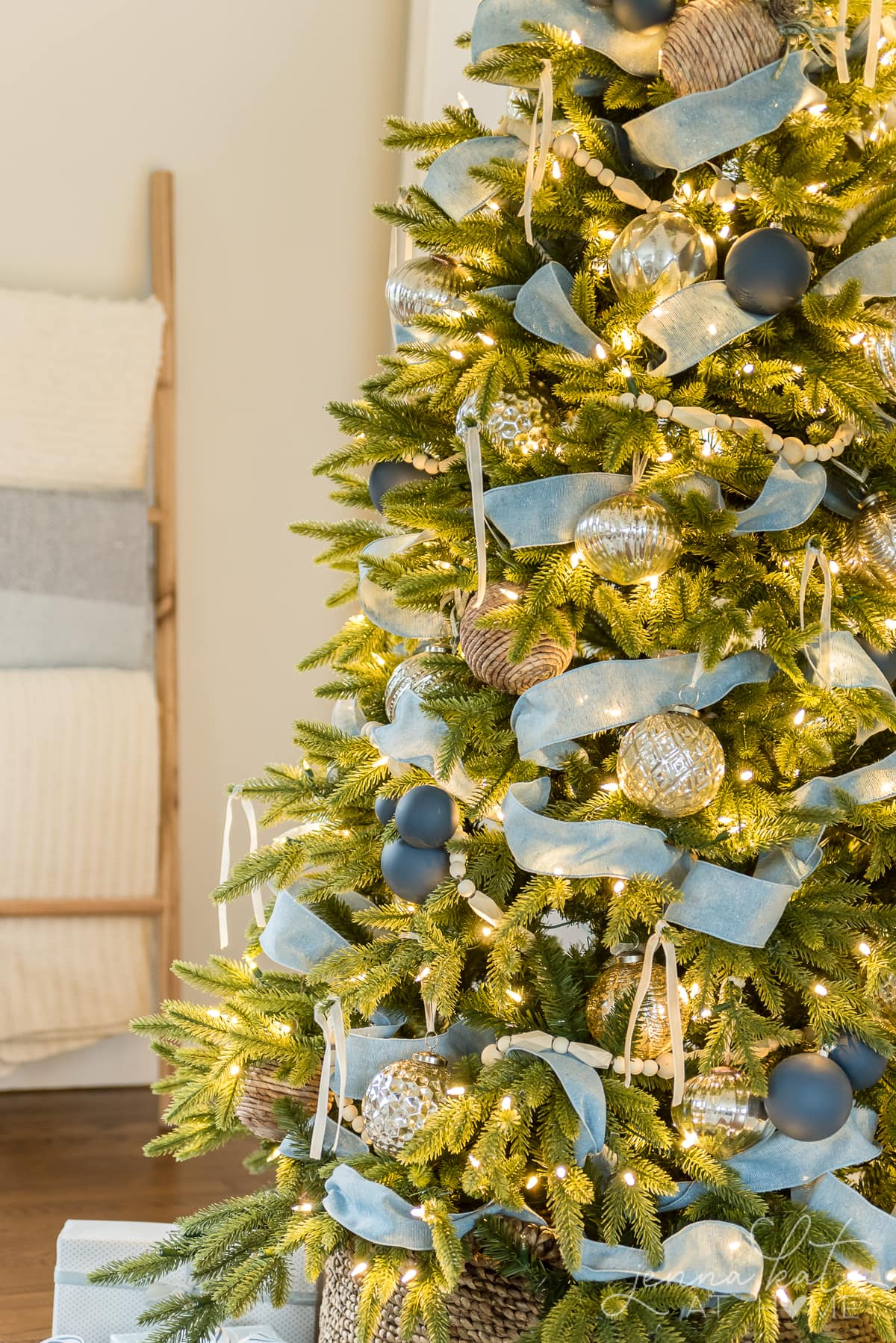 Close up of blue ribbon and blue ornaments as well as mercury glass balls on the Christmas tree