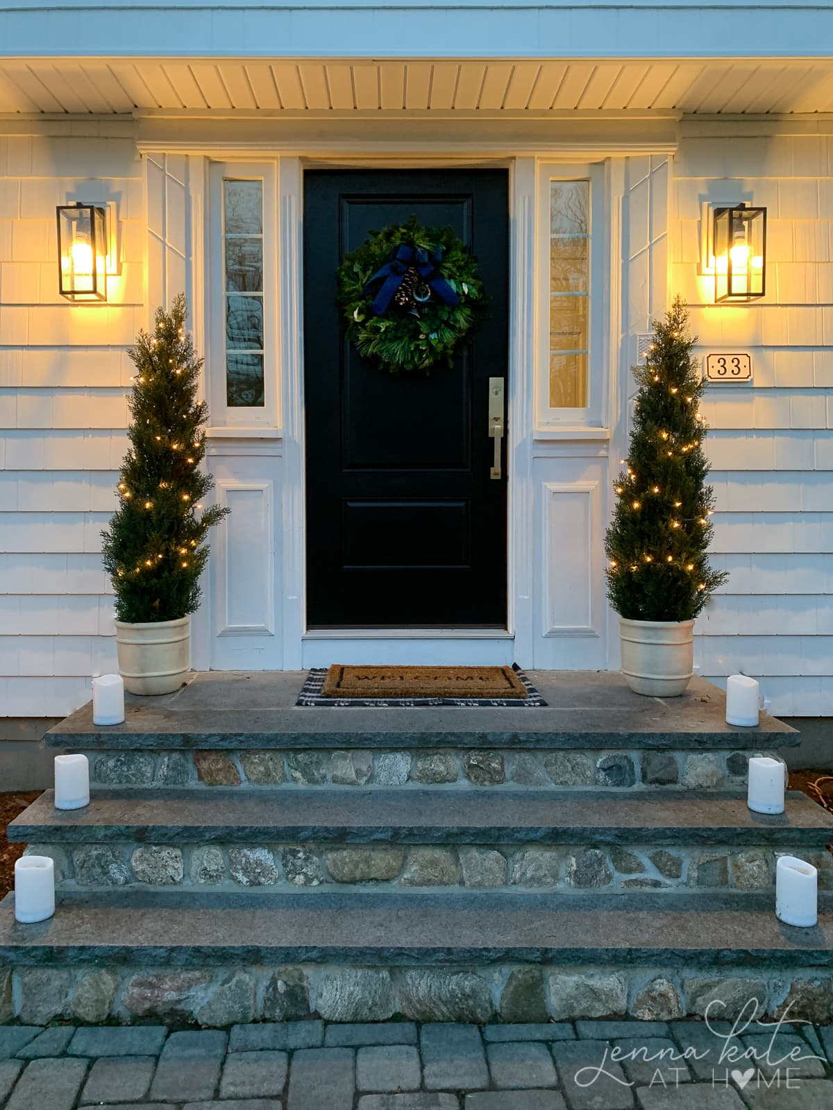 Black front door with a Christmas wreath and two mini trees on the front steps