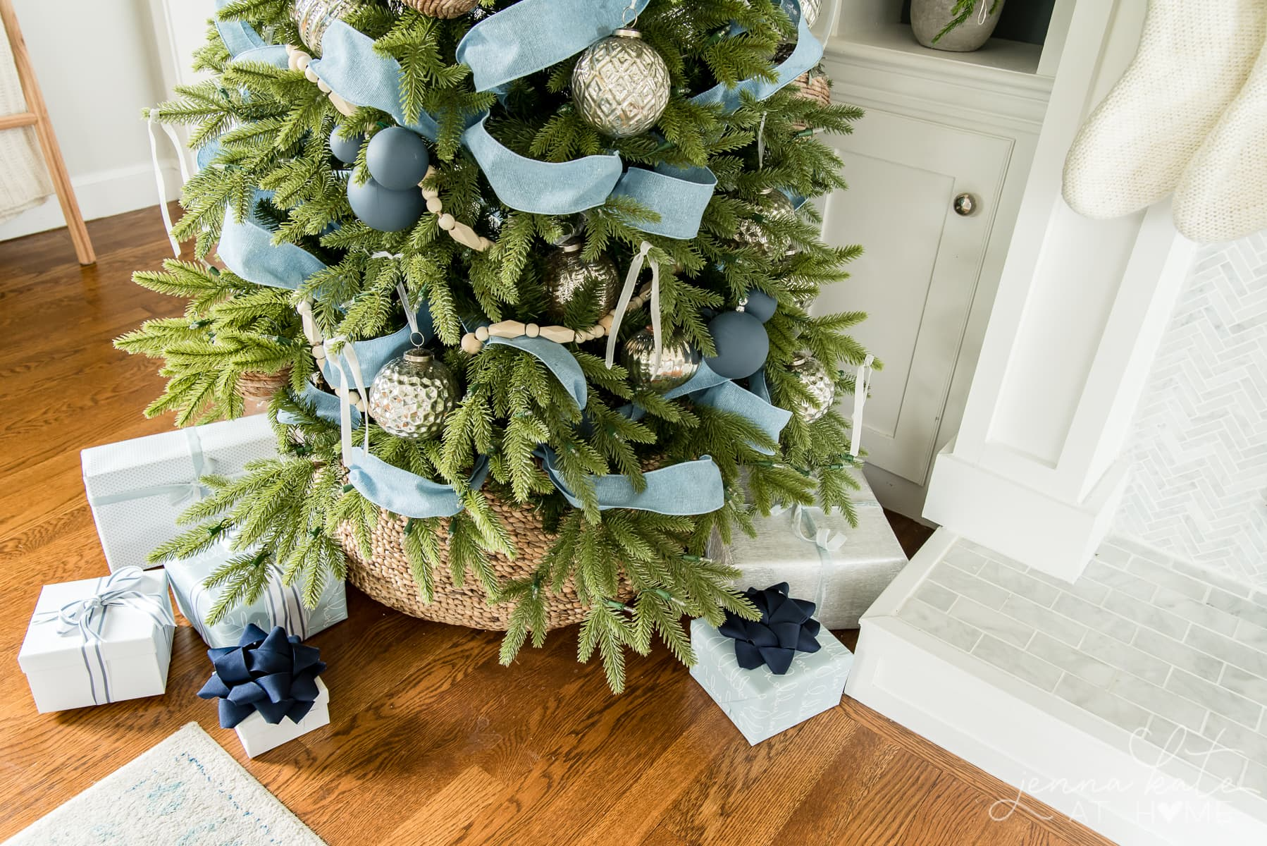 Presents wrapped under the Christmas tree with blue bows