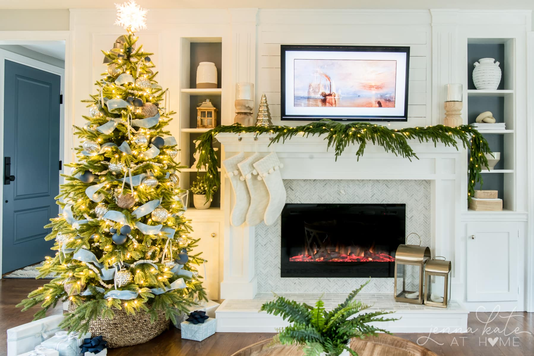 Living room fireplace mantel with green garland and Christmas tree decorating with blue and silver
