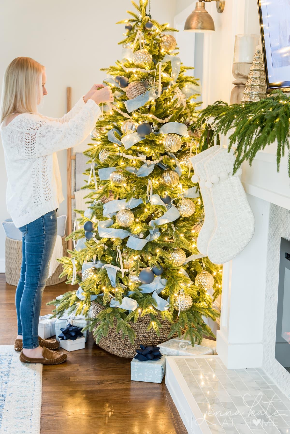Woman hanging ribbon on the Christmas tree