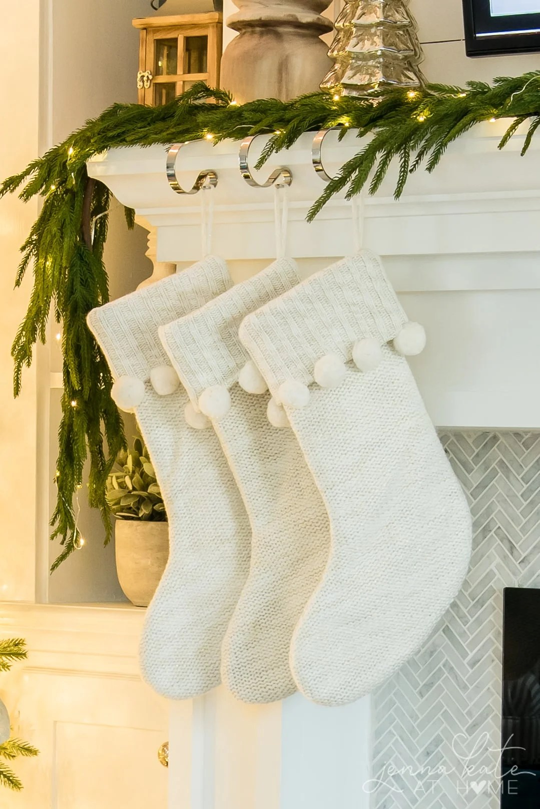 White knit stockings with pom poms hung on the mantel