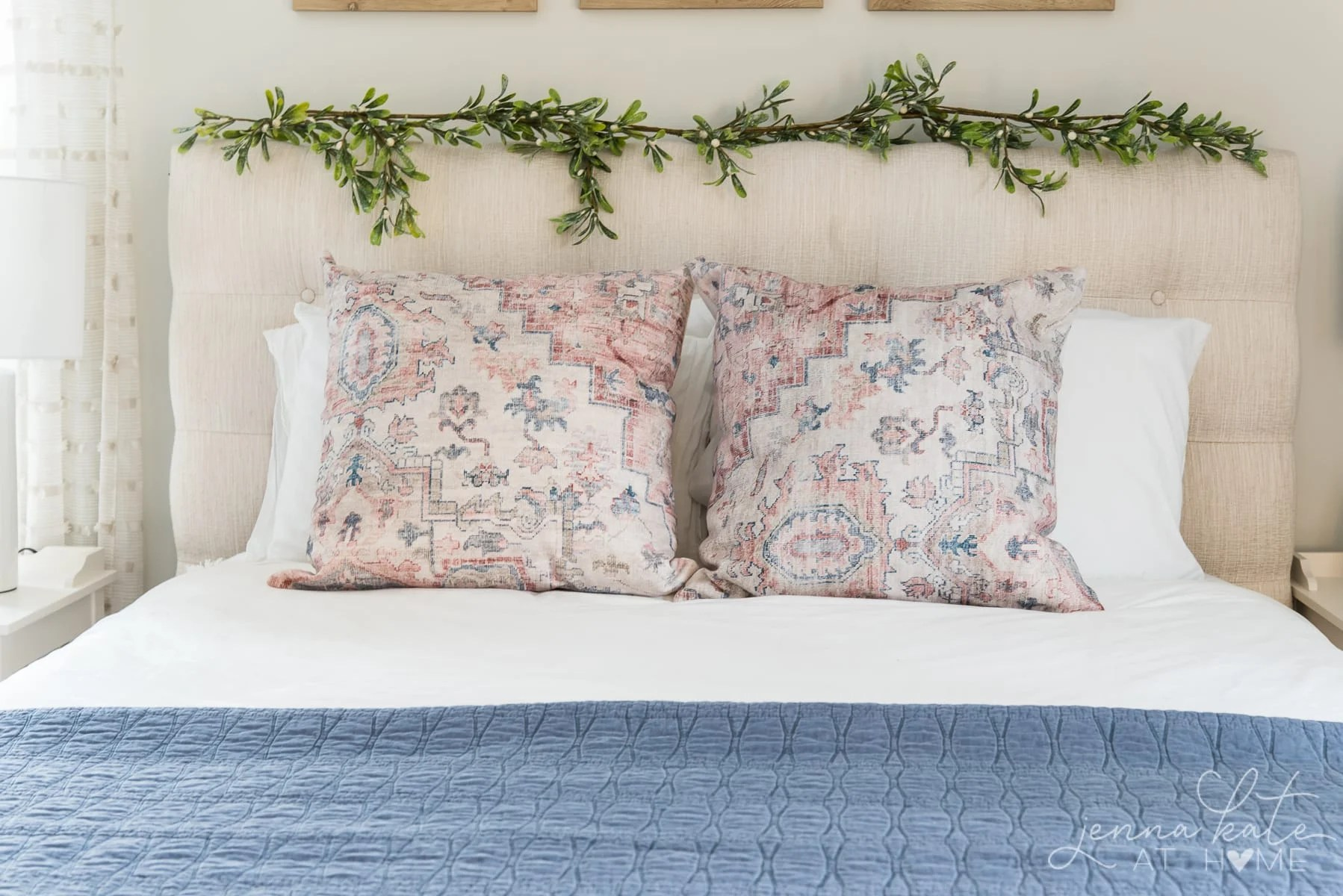 Pink and blue throw pillows on the bed with mistletoe garland on the headboard