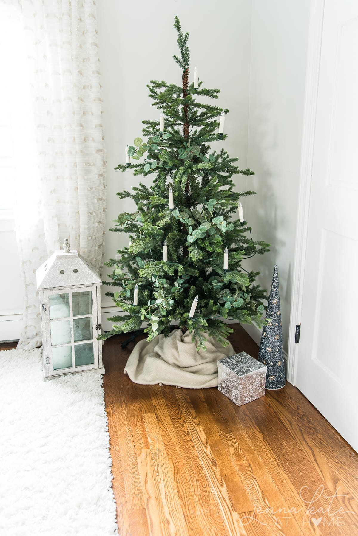 Small Christmas tree with candle lights and eucalytpus
