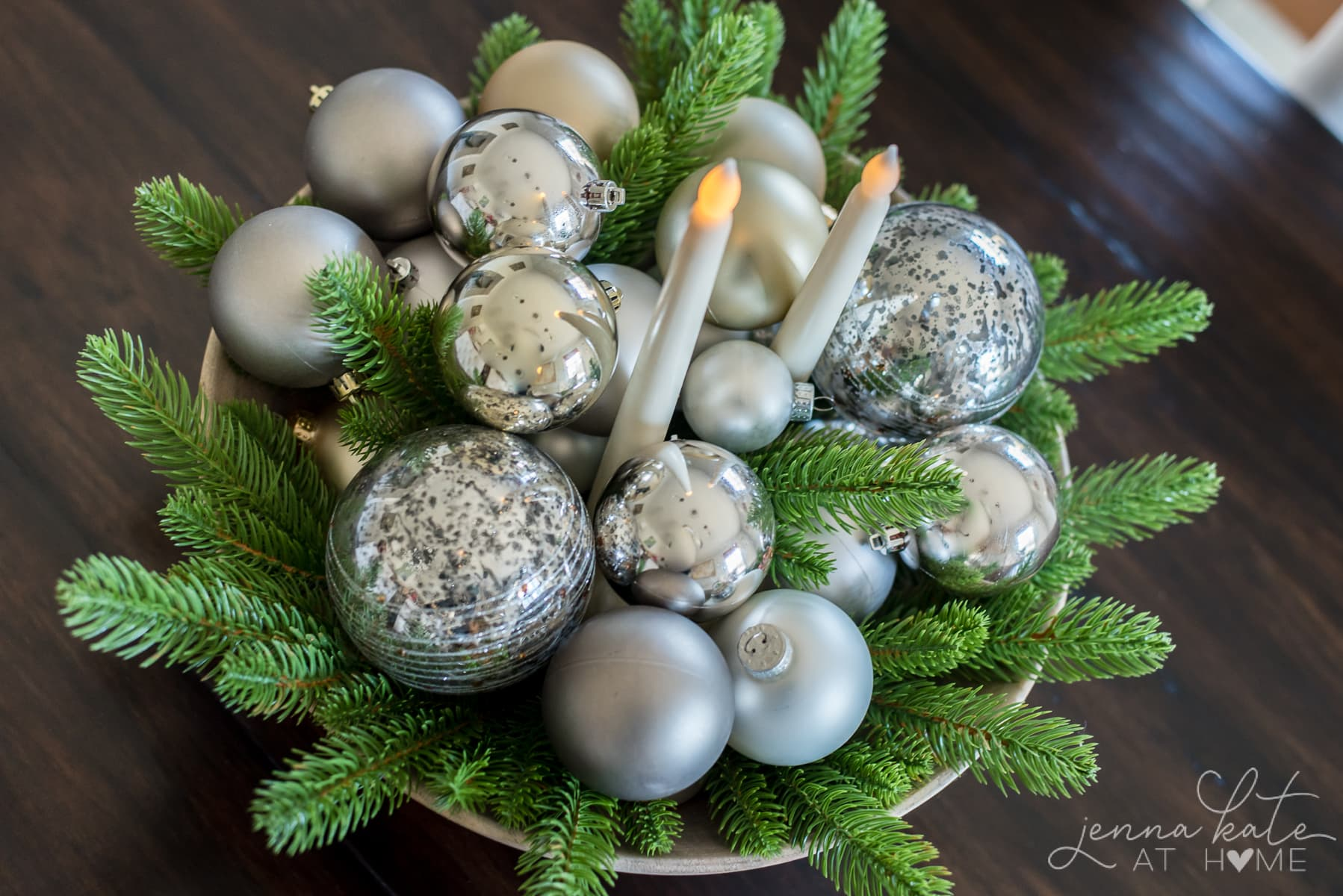An uncluttered minimalist center piece idea of a bowl filled with ornaments