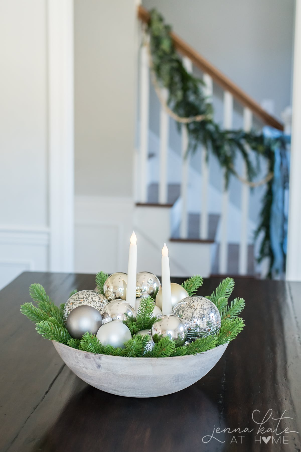 A bowl filled with greenery and ornament balls, with 2 battery operated candle in the middle