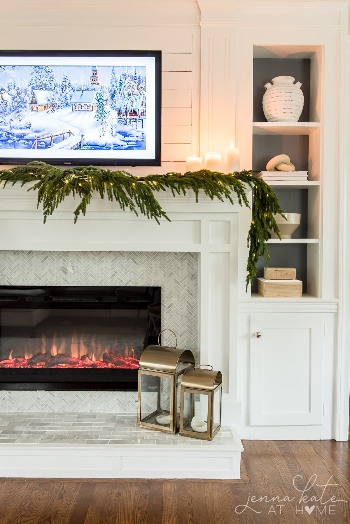 Pillar candles on a mantel surround by faux greenery