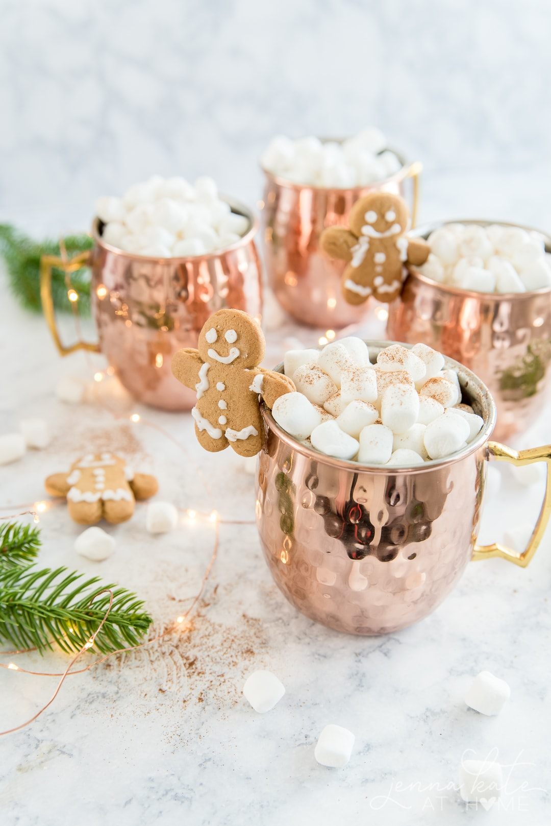Copper mugs filled with gingerbread hot chocolate and marshmallows with a gingerbread man mug buddy