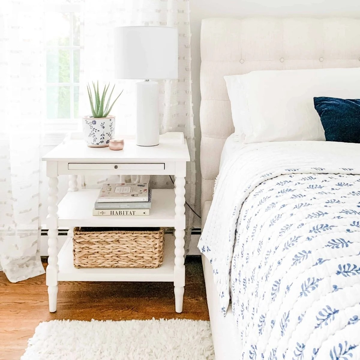 bedroom with white nightstand, white lamp and blue bedding