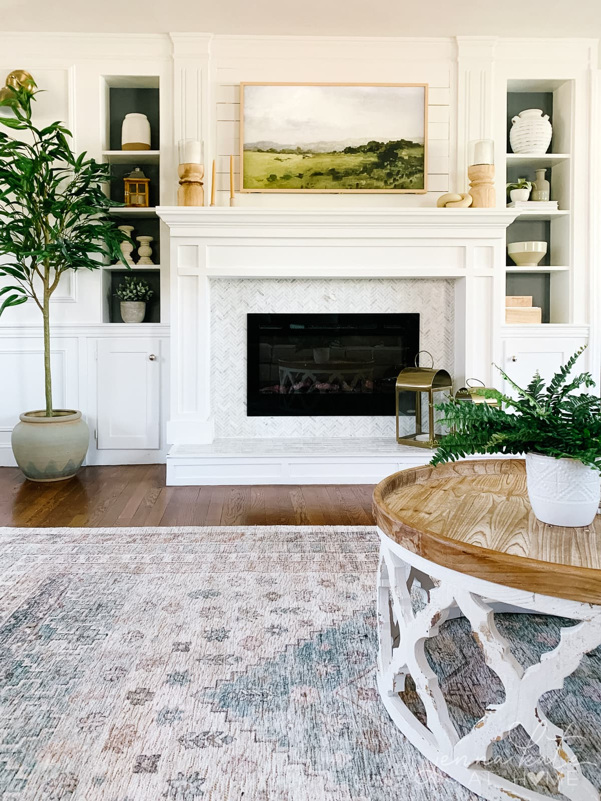 fireplace with frame tv hung over it displaying artwork