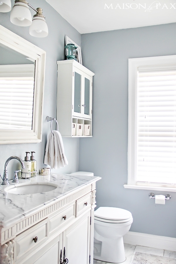 bright bathroom with marble topped vanity and blue-gray walls