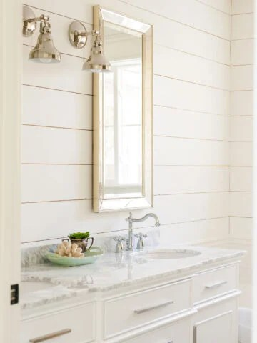 White shiplap adorns a small powder room wall, with large mirror and white sink below