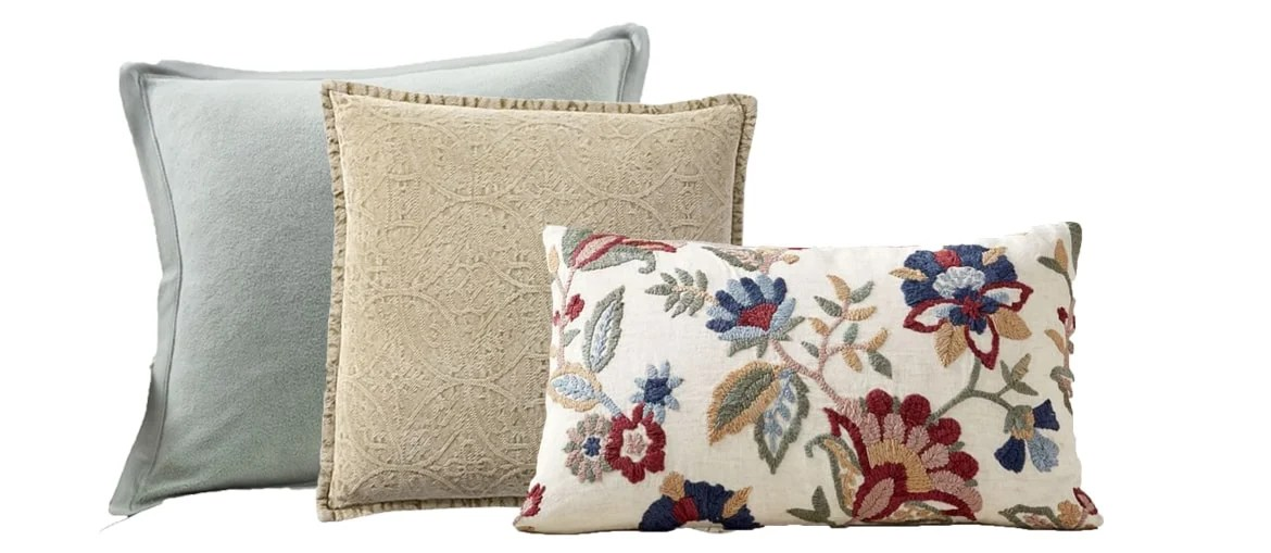 the floral lumbar pillow now paired with one green and one golden hued pillow