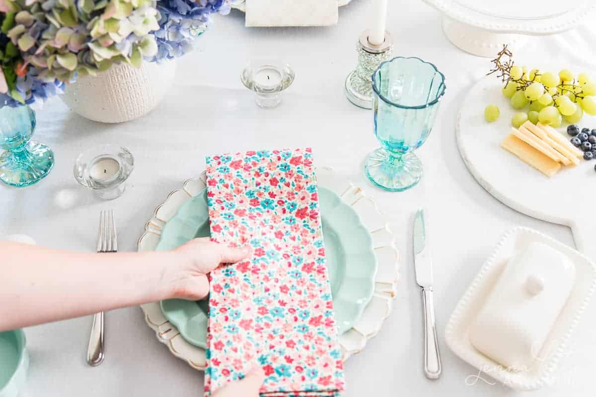 hand placing a floral napkin on a green plate as part of a spring table setting