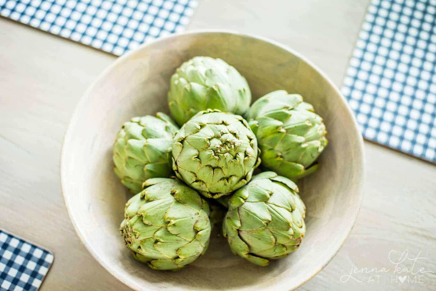 a bowl full of fresh artichokes as a spring table centerpiece