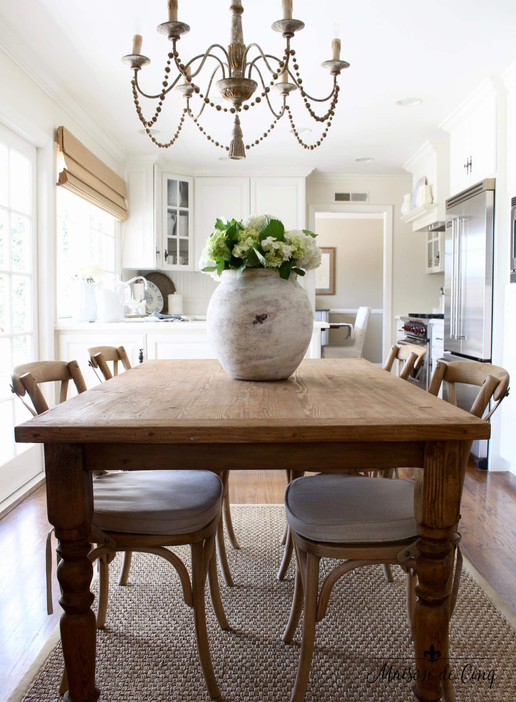 farmhouse table in the kitchen nook with  a large urn full of hydrangeas
