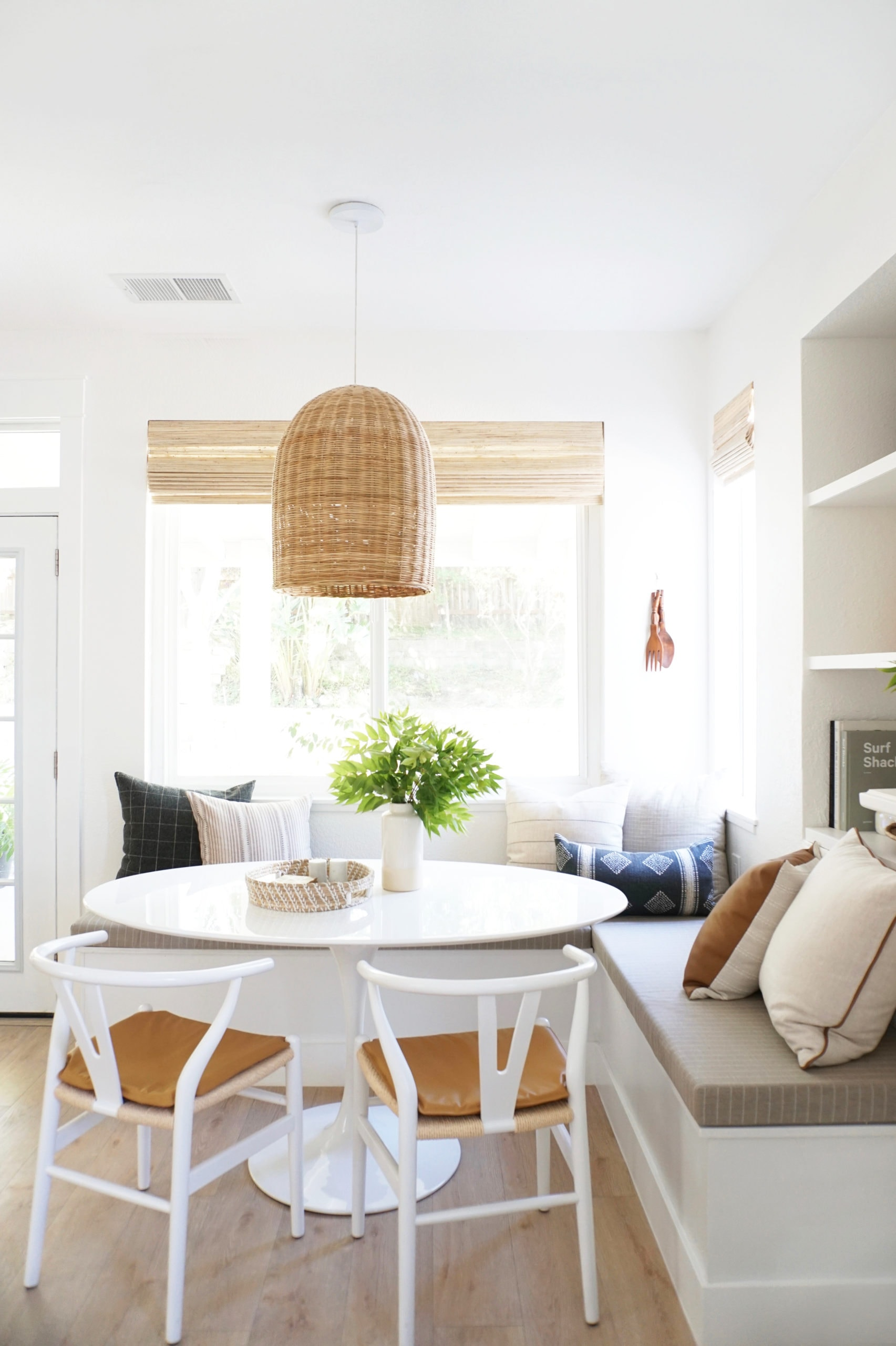 coastal style breakfast nook with large rattan pendant, upholstered bench and white tulip table