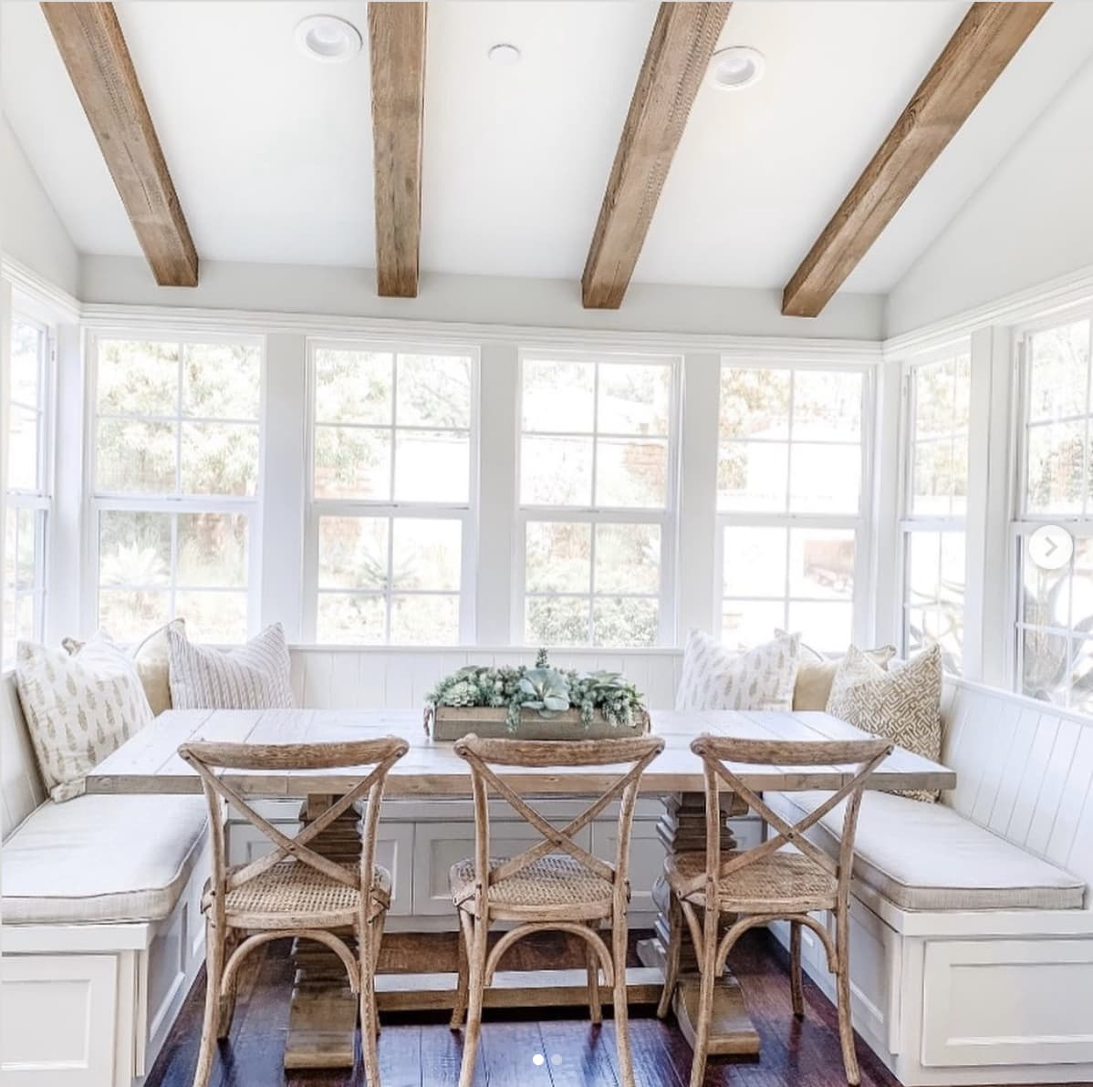 breakfast nook off kitchen with bay windows and rustic beams overhead