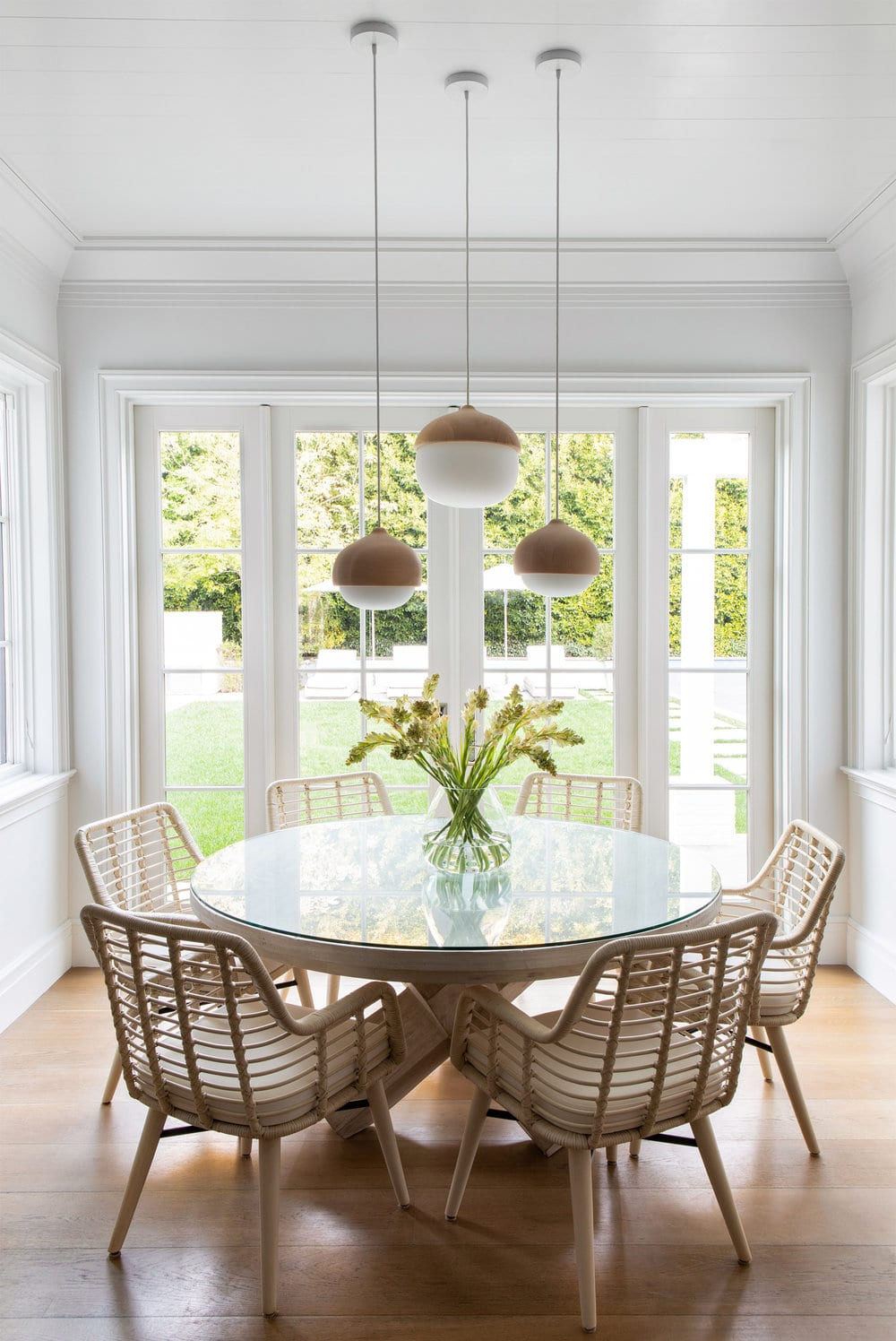 round pedestal table with rattan chairs and modern light fixture