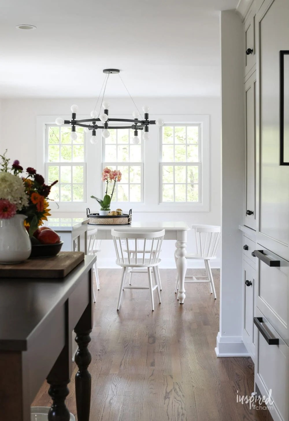 view of a white dining room set seen through a kitchen