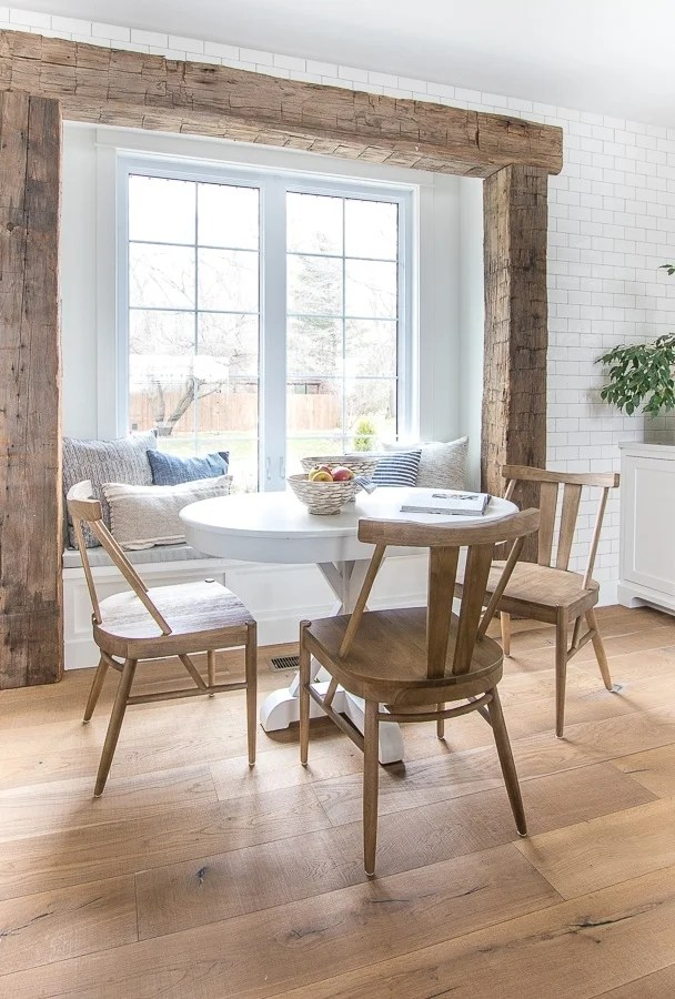 Recessed window framed out with chunky reclaimed wood beams and a white table and upholstered bench for the breakfast nook