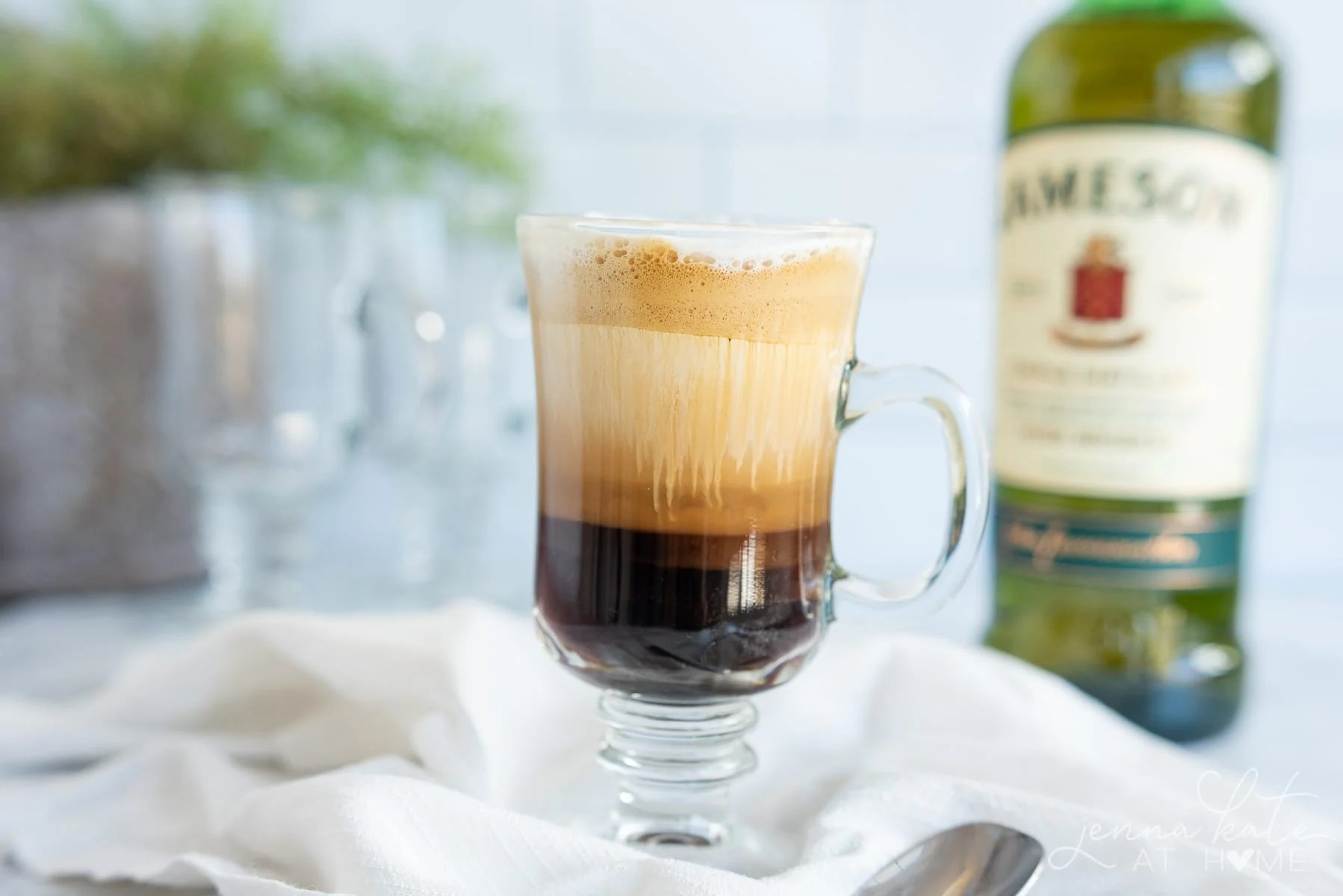 Glass of Irish coffee with a bottle of Jameson Irish whiskey in the background