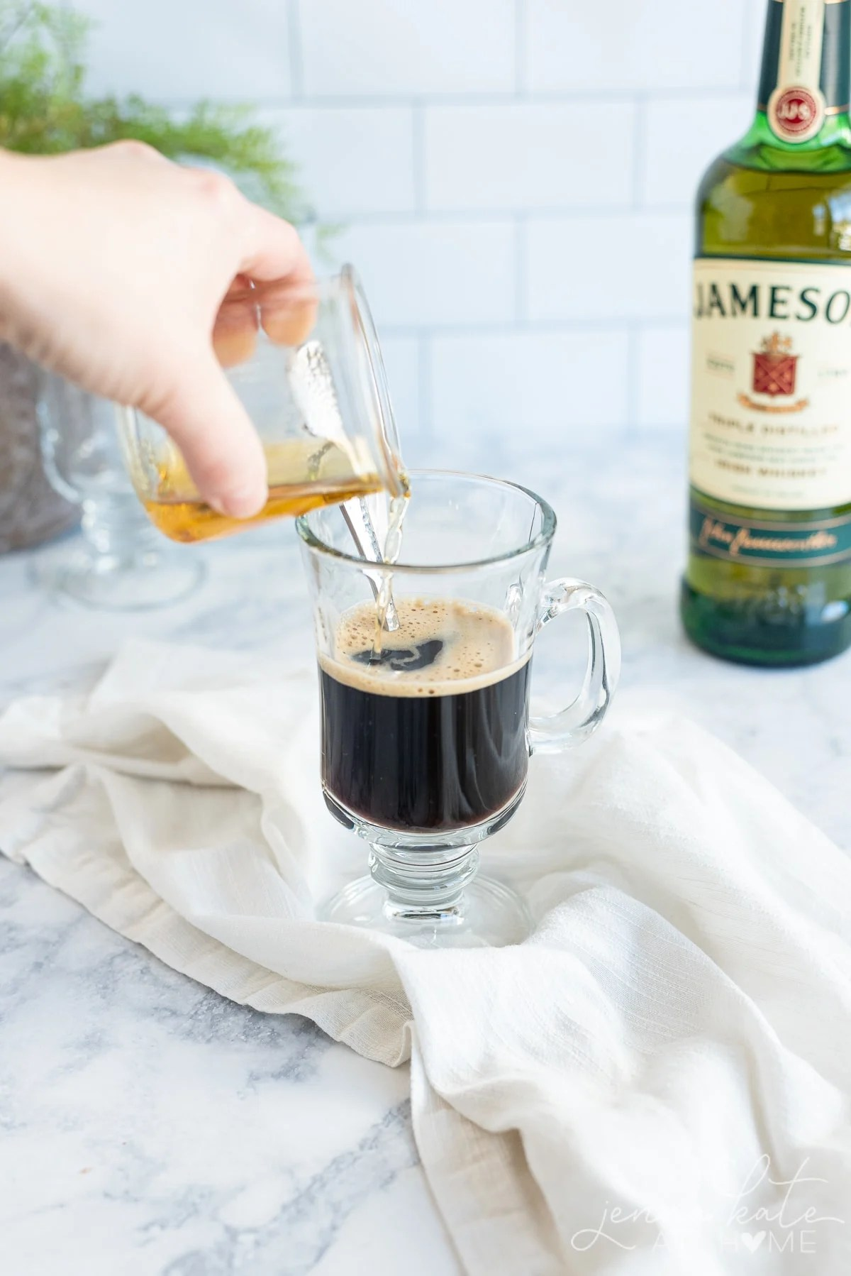 Pouring whiskey into the black coffee