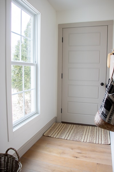 mudroom with white walls and warm greige trim and door