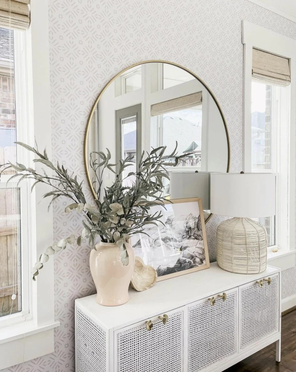 large round mirror over a console table