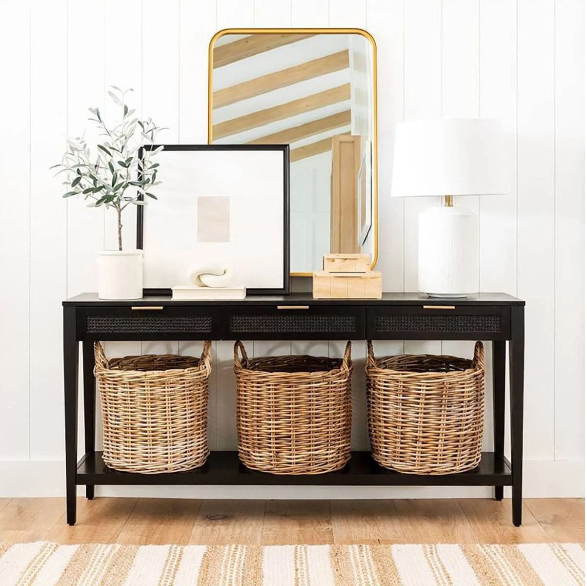 black console table with layered mirror, artwork and table lamp