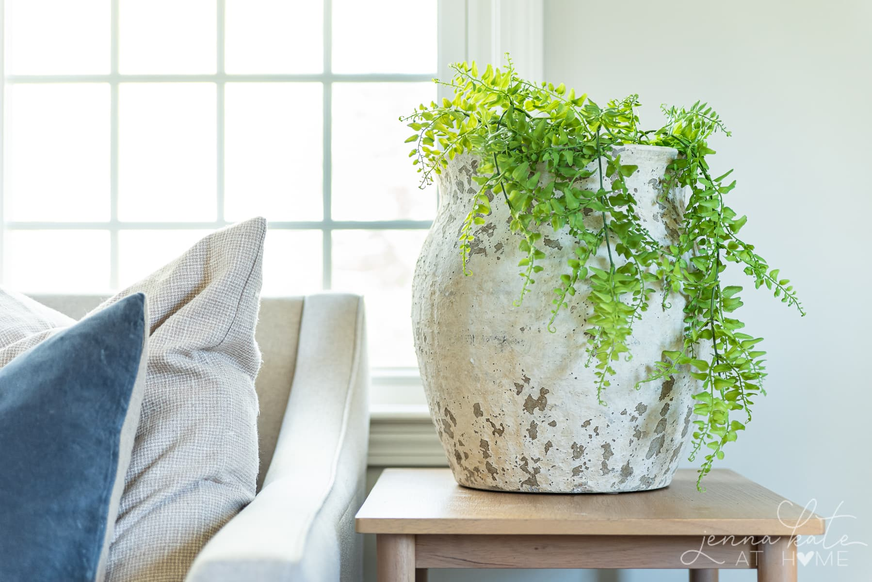 living room side table with a large oversized vase with trailing green plant