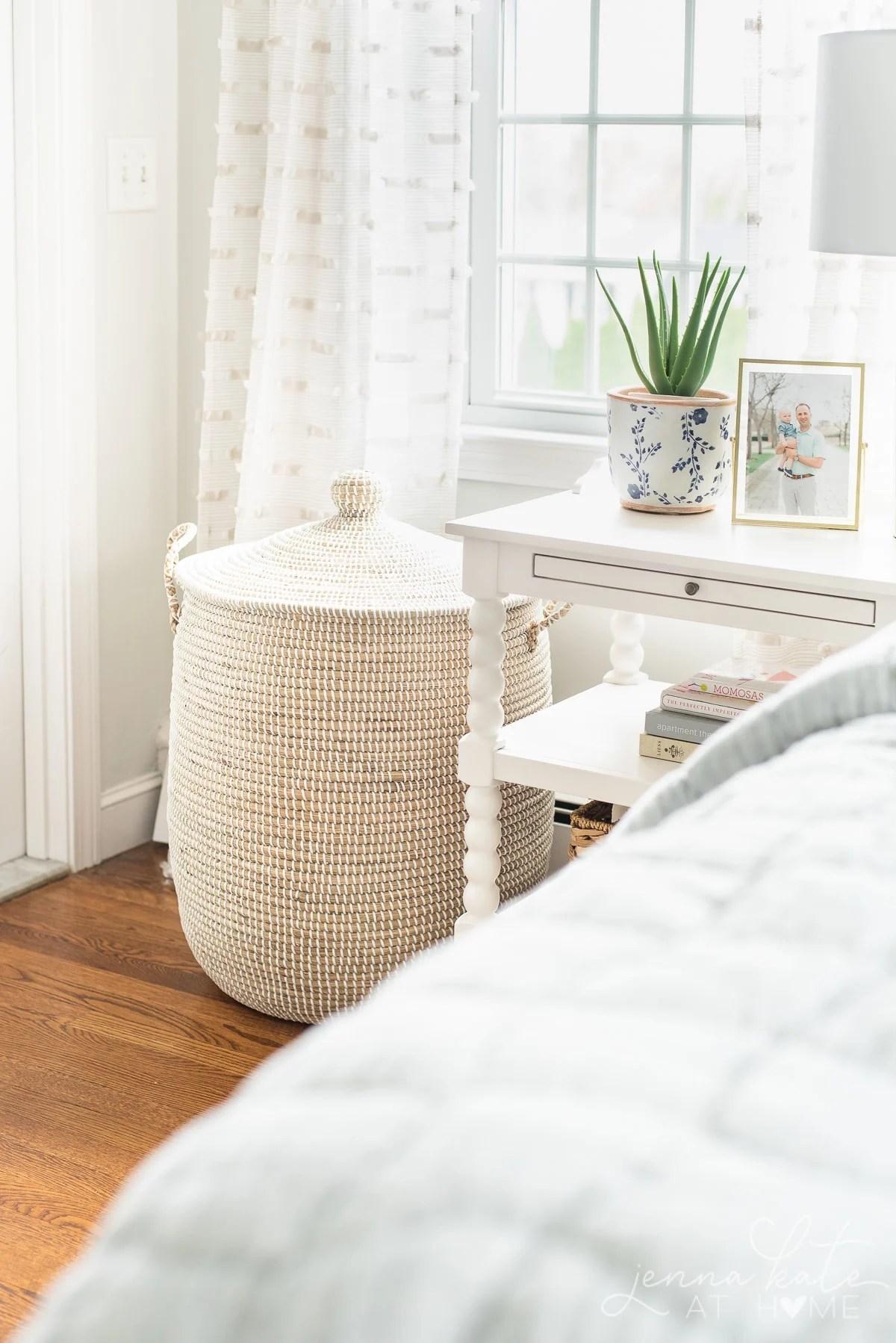 rattan linen basket in the corner of a bedroom