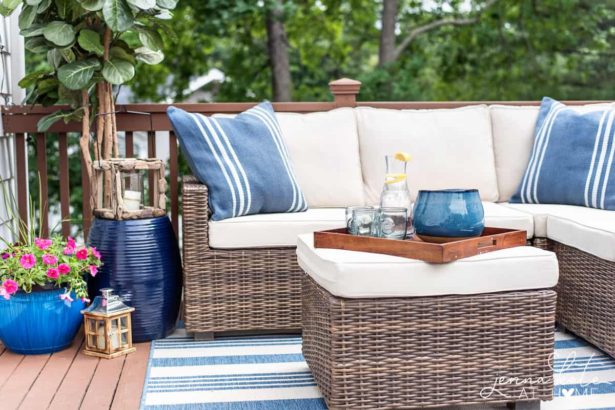 Deck decorated for summer with a sectional with blue throw pillows