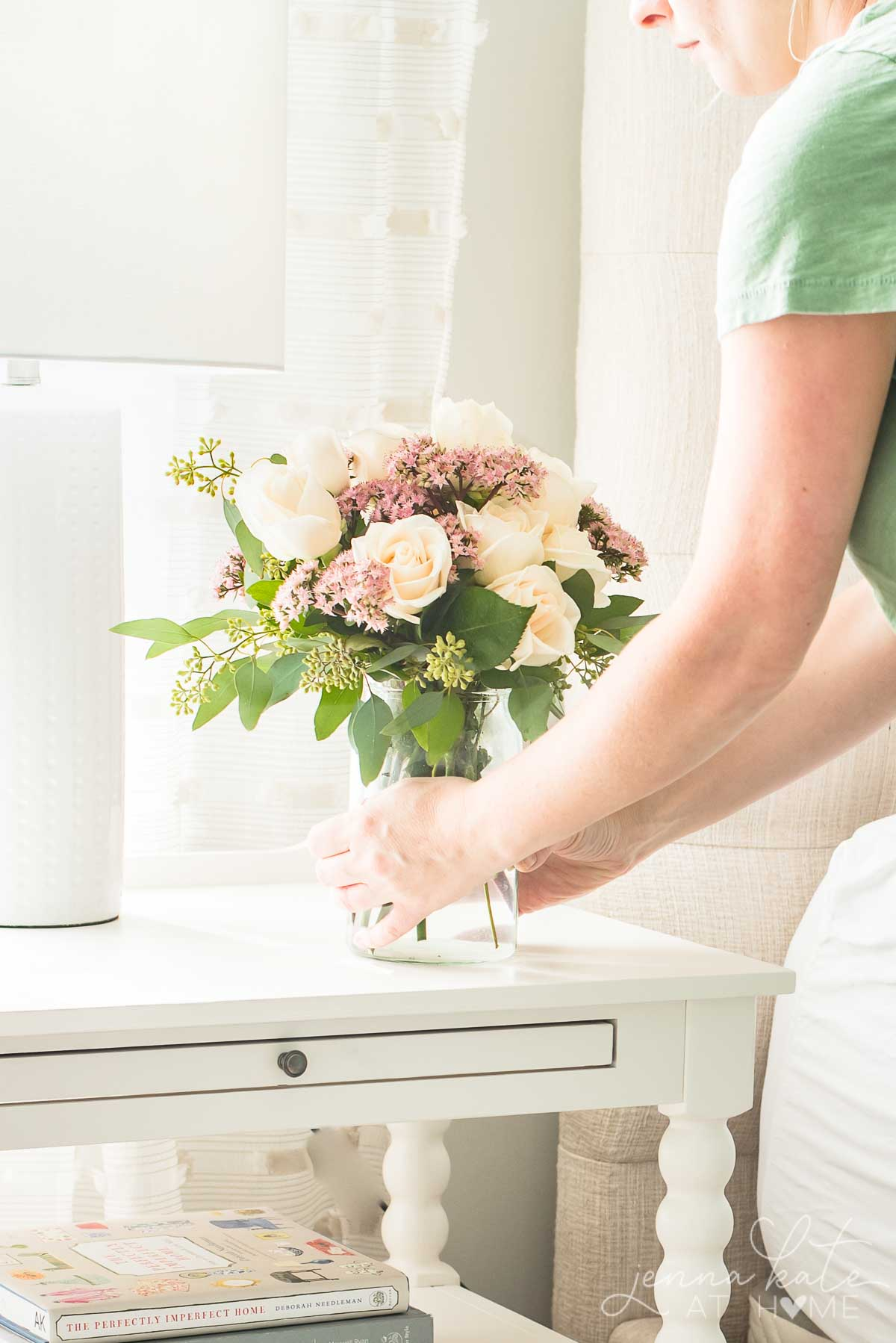 bedroom nightstand with woman placing vase of summery flowers on it