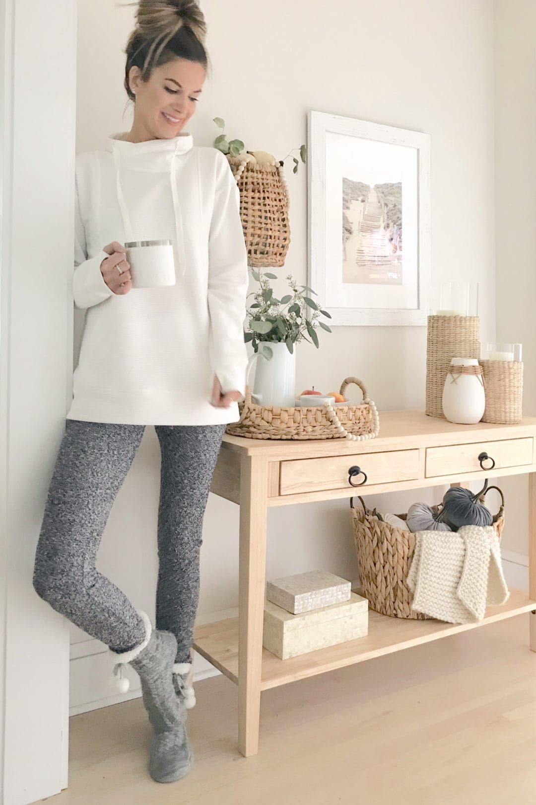 woman standing next to light wood console table with the background wall painted classic gray