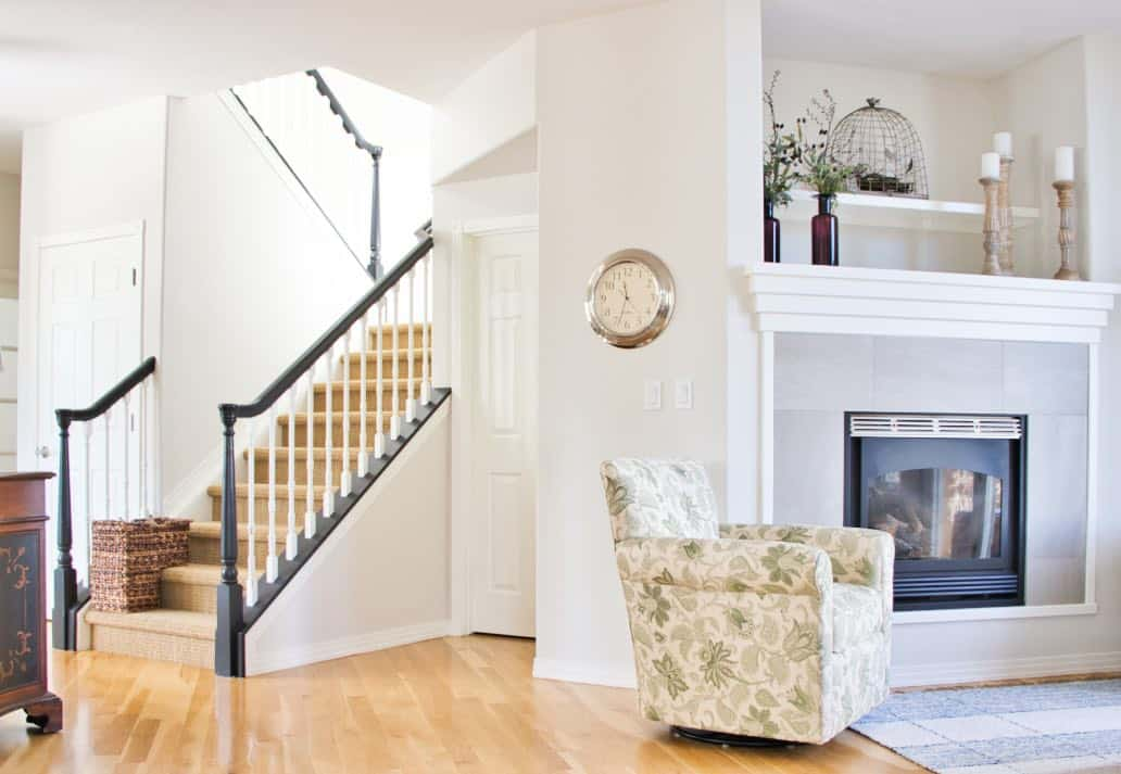 living room open to foyer with warm oak floors and staircase with black railings