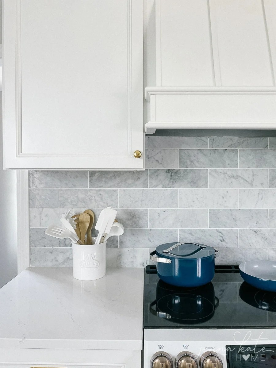 white quartz counter tops, marble backsplash and white cabinets