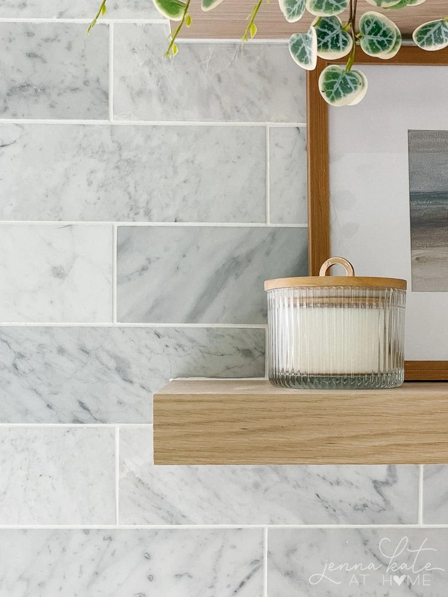 carrara marble backsplash and oak floating shelf