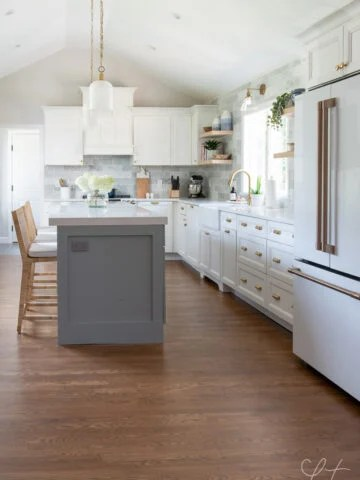 kitchen with white cabinets, blue island and brass accents