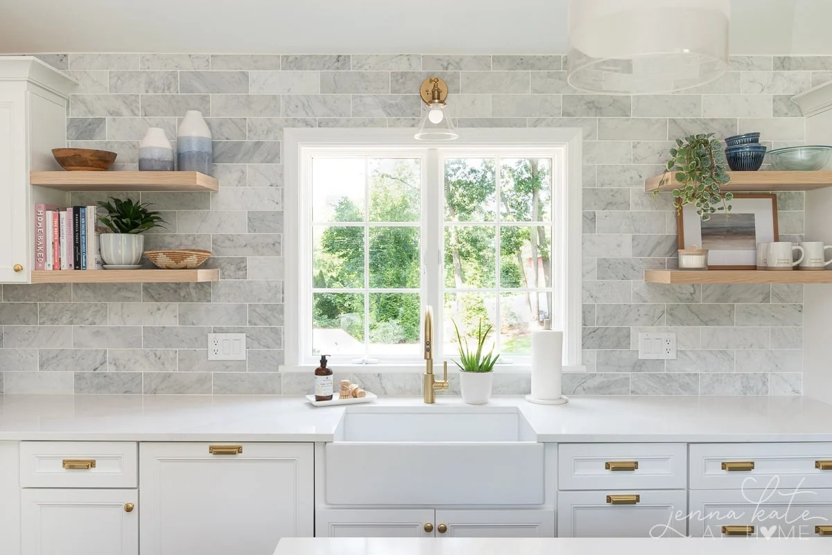 picture window over sink with shelves on either side