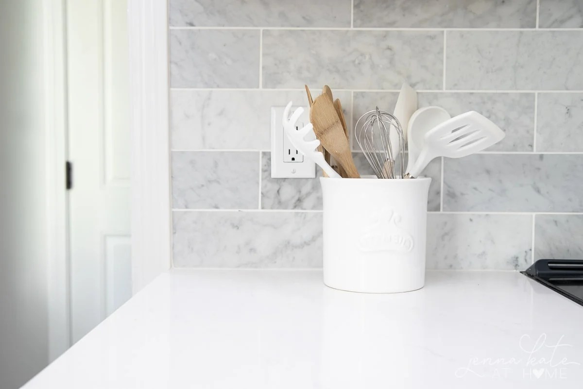 white kitchen countertop with marble backsplash and utensil crock