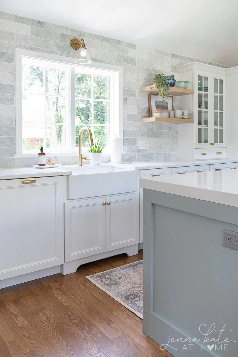 farmhouse kitchen sink and marble subway tile to the ceiling