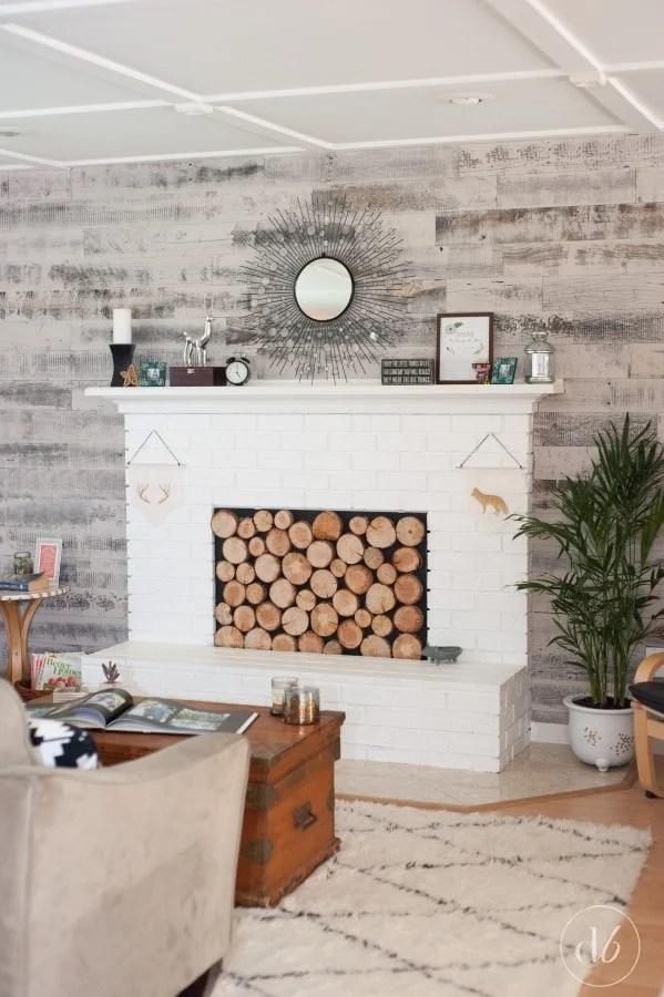 white brick fireplace with rustic reclaimed wood accent wall