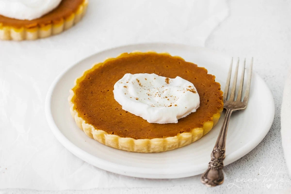 mini pumpkin pie on a plate with a fork