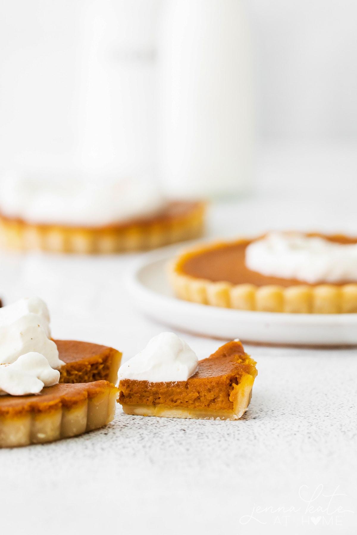 a slice taken out of one mini pumpkin pie tart